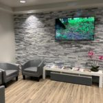 Photo of our front office lobby with comfortable couches and large screen TV
